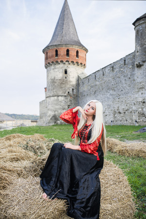 Beautiful young blond woman pose near medieval castle. Stock Photo