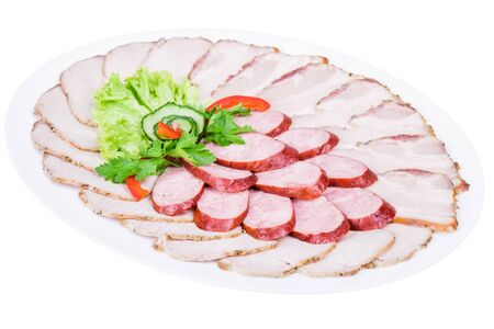 Isolated cutting of meat and sausage decorated with greens