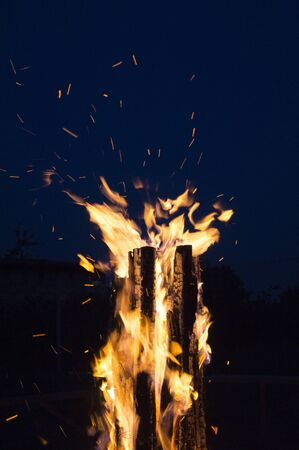 Big bonfire against blue night sky.