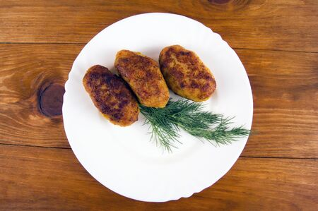 Fish patties in a white plate with greens on a wooden background 스톡 콘텐츠