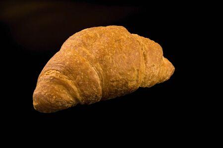 Fresh, appetizing croissant on a dark background