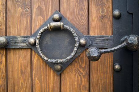 decorative frame with handles in the shape of a ring on a wooden gate background Foto de archivo