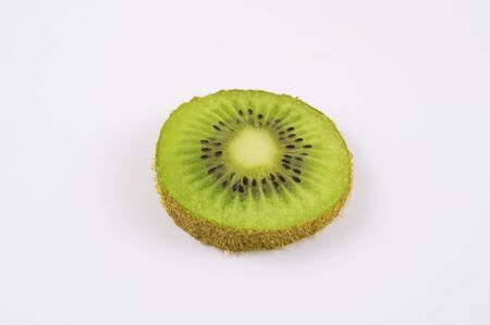 Slice of green kiwi on a light background