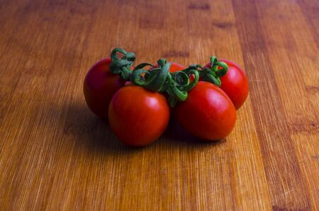 Several cherry tomatoes on a wooden board