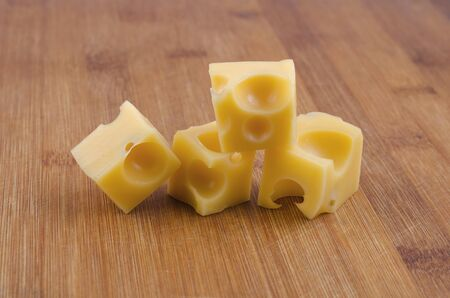 Cheese cubes on wooden background