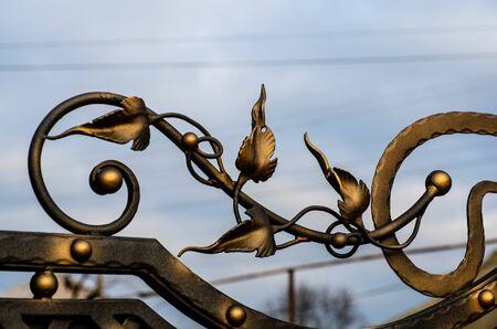 Metalowe liście zdobiące kute bramy