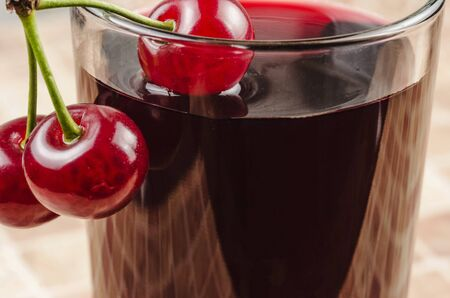 A glass of cherry juice with ripe cherries