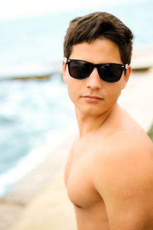 ni�o sin camisa: Joven hombre musculoso en gafas de sol a orillas del mar