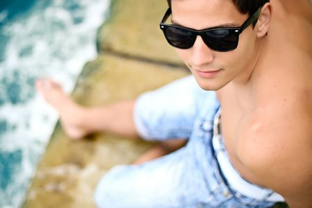 sexy young trendy man in sunglasses on the beach. Focus on sunglasses. photo
