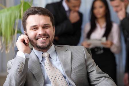 Laughing executive businessman on the phone while his team is working behind Stock Photo - 9282996