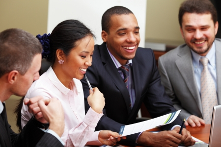 Multi ethnic business team at a meeting. Interacting. Focus on woman photo