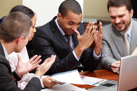 Multi ethnic business team at a meeting. Interacting. Focus on african-american man photo