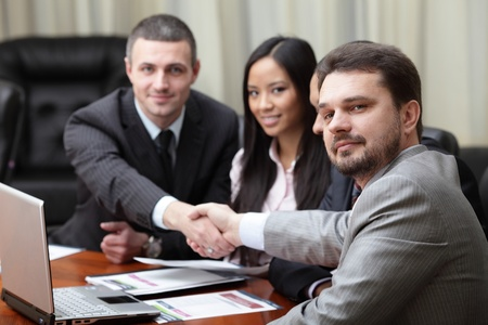 Multi ethnic business team at a meeting. Interacting. Focus on caucasian man in front Stock Photo - 9282676