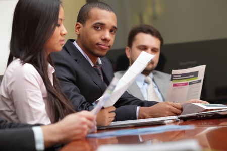 Multi ethnic business team at a meeting. Focus on african-american young man Stock Photo - 9282886