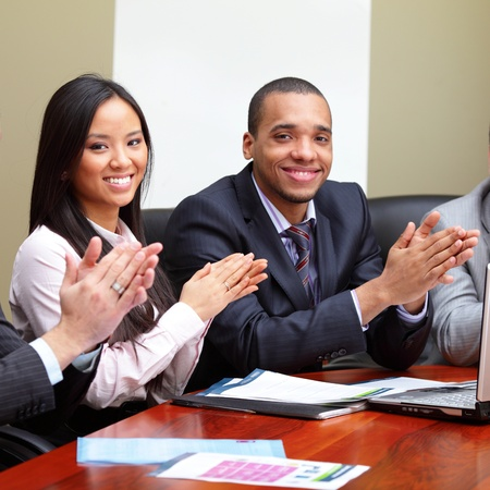 Multi ethnic business group greets you with clapping and smiling. Focus on woman Stock Photo - 9282529