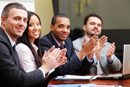 Multi ethnic business group greets you with clapping and smiling. Focus on woman photo