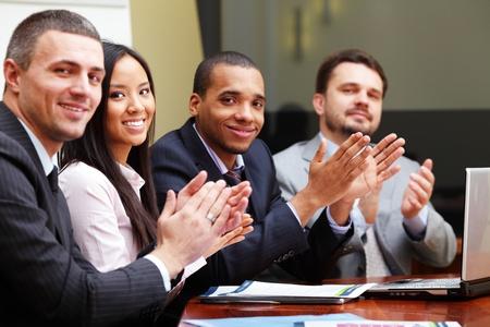 saluta: Multi etnica business group vi accoglie con battimani e sorridente. Concentrarsi sulla donna Archivio Fotografico