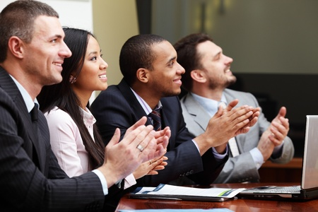board meeting: Multi ethnic business group greets somebody with clapping and smiling. Focus on woman Stock Photo
