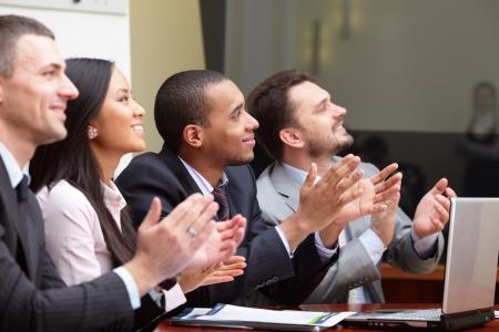 conferentie: Multi-etnische bedrijfsgroep begroet iemand met klappen en glimlachend. Focus op Afro-Amerikaanse man Stockfoto