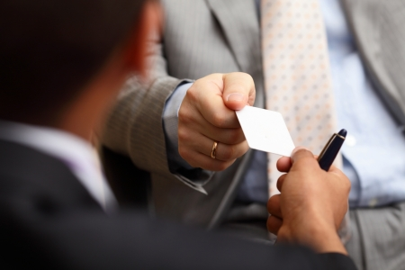 Closeup portrait of two successful business executive exchanging business card photo