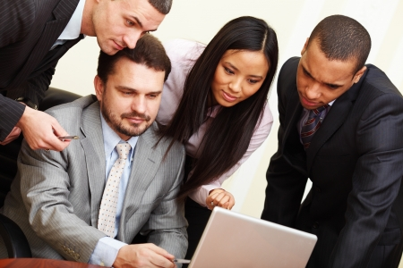 Mature businessman shows something on laptop to his multi ethnic business team Stock Photo - 9283097