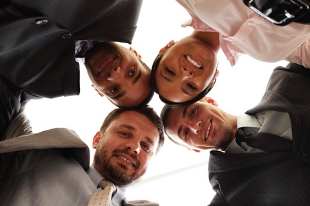 Mixed businessteam with heads together over white photo