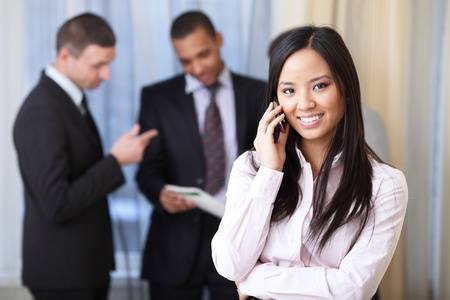 new employee: Portrait of young happy asian woman on phone with her business partners on the background