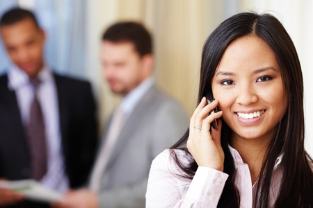 Portrait of young happy asian woman on phone with her business partners on the background photo