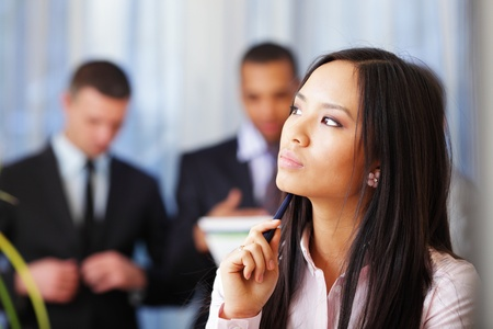 Portrait of young pensive asian woman with her business partners on the background photo