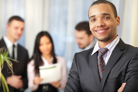 Happy african-american businessman with his team working behind Stock Photo - 9282809
