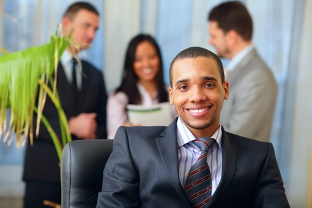 Happy african-american businessman with his team working behind Stock Photo - 9282655