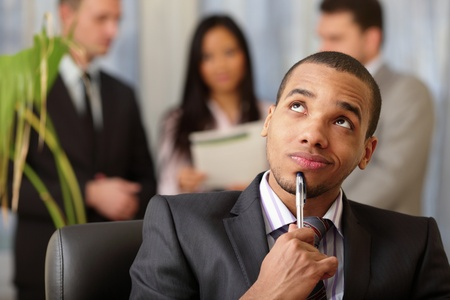Pensive african-american businessman with his team working behind photo