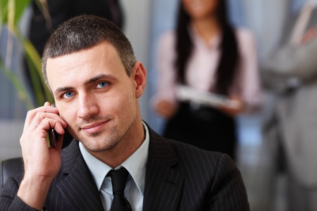 Handsome executive businessman on the phone while his team is working behind photo