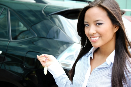 Young attractive asian businesswoman closes the door of her car  Stock Photo