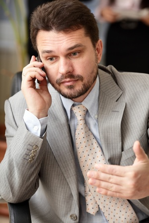 Portrait of a mature business man screaming in his cellphone in office environment photo