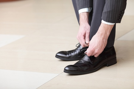 mens: Man ties his shiney new black leather business shoes.