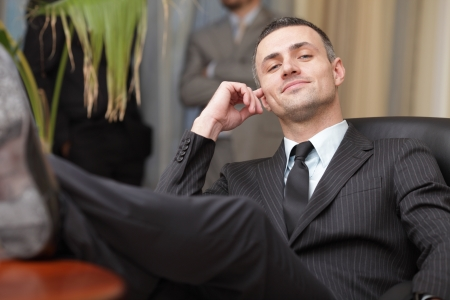 feet on desk: businessman relaxing at the office with his shoes on the desk