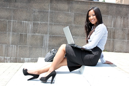 Woman on laptop outside in the city Stock Photo - 9282932