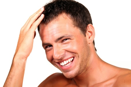 hair shampoo: Closeup of a happy young man looking at camera and touching his hair