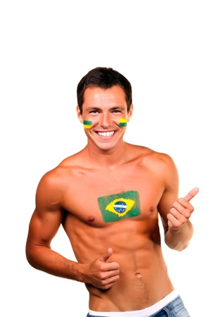 Cheerful happy brazilian football fan with flag on his body and face, isolated on white photo