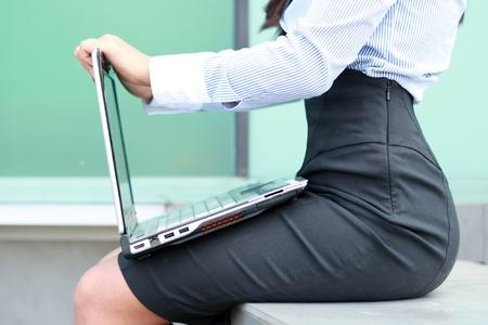 segretario: donna sulla strada seduto con un computer portatile in grembo e digitando  Archivio Fotografico