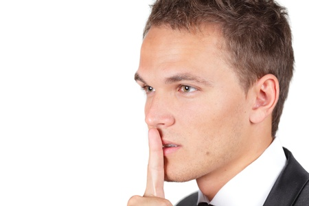 noiseless: Portrait of businessman showing silence gesture with his forefinger by mouth looking asiade Stock Photo