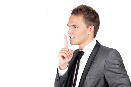 noiseless: Portrait of a young businessman showing silence gesture with his forefinger isolated