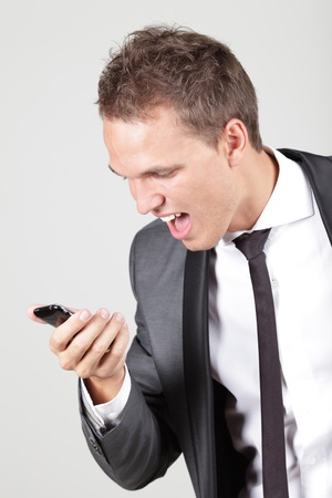 Profile view of a young business man screaming in his cellphone over white photo