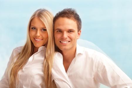 pareja en casa: Feliz pareja abraz�ndose en casa con una hermosa vista al mar detr�s de su ventana