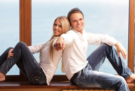 Young loving couple holding hands, sitting at the window and smiling Stock Photo - 9282913