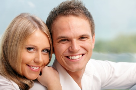Young happy couple hugging at home with a beautiful seaview behind their window Stock Photo - 9282510