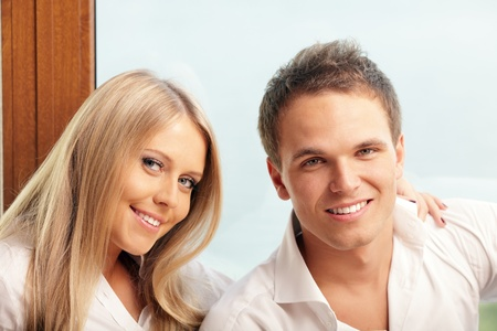 Young happy couple relaxing at home with a seaview behind their window Stock Photo - 9282928