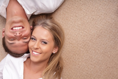 Portrait of a young couple lying on the floor with their heads close to each other Stock Photo - 9283027