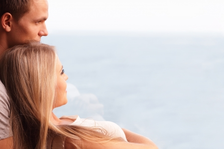 Young loving couple embracing and looking at a beautiful seaview in the window photo